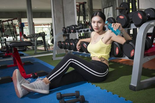 Young asian women sitting relaxing after training with Mineral drink