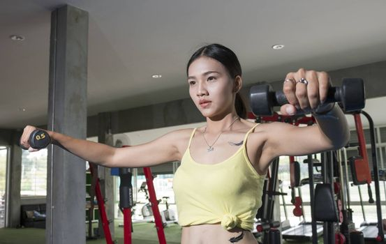 Asian sport women with dumbell in gym
