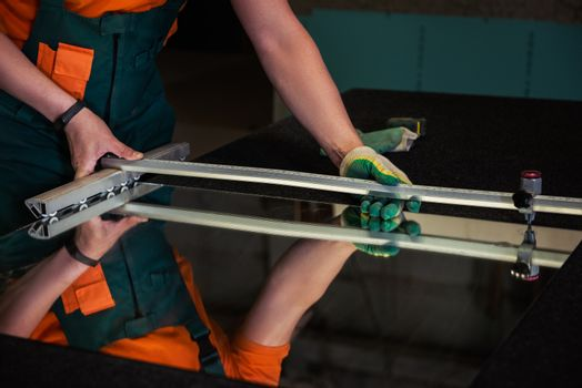 Furniture production. Worker cutting the surface of glass mirror for the furniture production