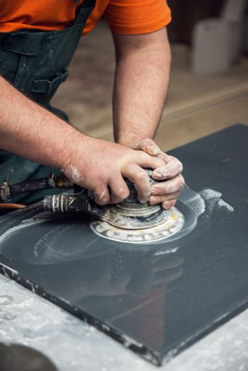 Stone furniture production. Worker polishes the surface of the facade with a grinder