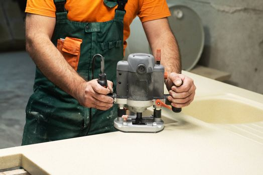 Stone sink furniture production. Worker polishes the surface of the sink with a grinder