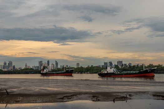 Bangkok, Thailand - 11 May 2020 : Two cargo ship parked in the middle of the Chao phraya river on evening sky background.