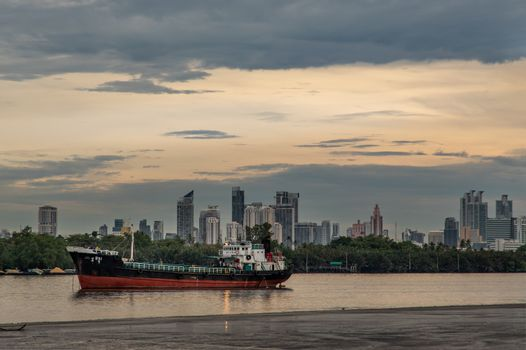 Bangkok, Thailand - 11 May 2020 : A cargo ship parked in the middle of the Chao phraya river on evening sky background.