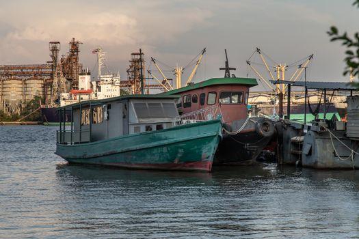 Bangkok, Thailand - 26 Mar 2020 : Cargo ships in the middle Chao Phraya river near the small pier.