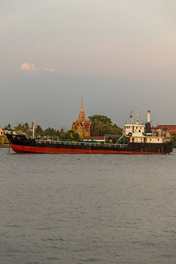 Bangkok, Thailand - 26 Mar 2020 : Two cargo ship parked in the middle of the river and in front of a green tree by the Chao Phraya River.