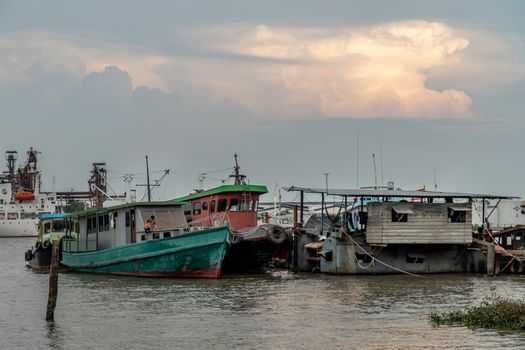 Bangkok, Thailand - 10 Apr 2020 : Cargo ships in the middle Chao Phraya river near the small pier.