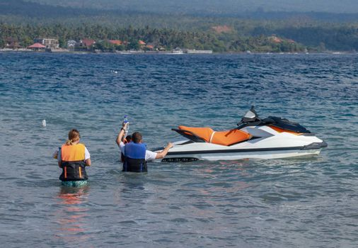 Tourists enjoy driving jet ski on the ocean. A young couple boardes a jetbike.