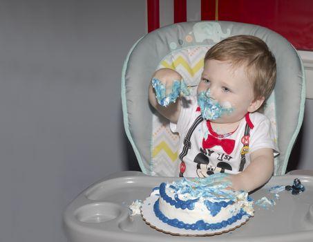 Toddler celebrating first birthday with smash cake.