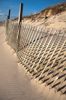 Fence Sandy beach. Cloudy sky.