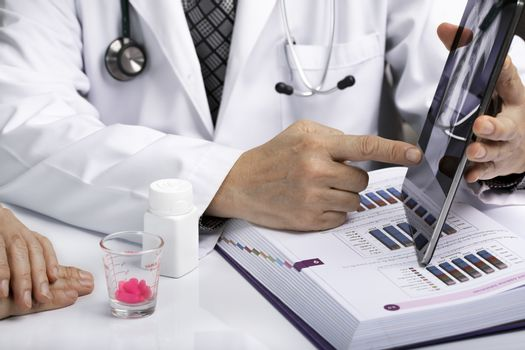 An asian male doctor using a tablet to discuss examination results with a patient.