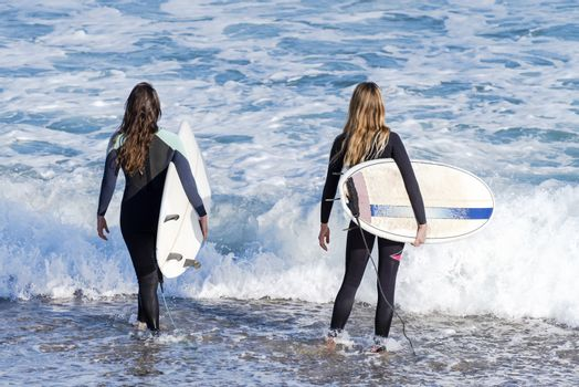 Two sporty surfing girlfriend with big longboard surf surfboard board. Modern active sport lifestyle and summer vacation. Long hair women.