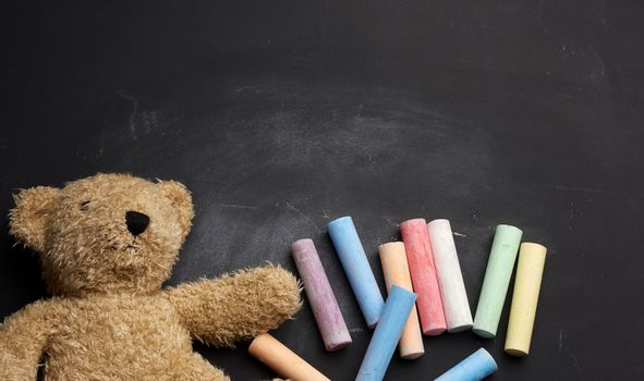 brown teddy bear and colorful crayons on black chalk board, back to school