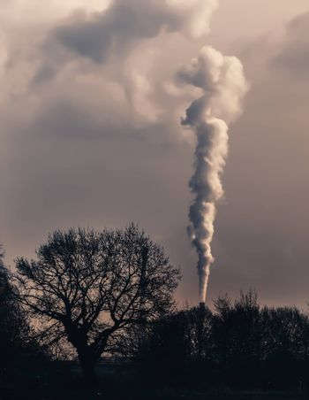 Smoke emission from chimney. Cause of global warming. Conception of air pollution and smog issue. Factory steam contaminate atmosphere. Fumes from burning carbon cause climate change problems .