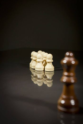 Chess pieces on a black reflective surface