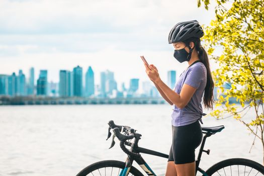Biking cyclist using mobile phone for contact tracing app wearing COVID-19 face mask as coronavirus prevention while riding road bike outside on city travel vacation eco-tourism.