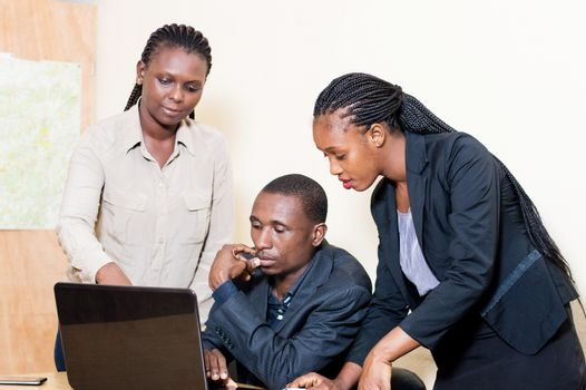 Three business partners working on a laptop in the office and sharing knowledge.