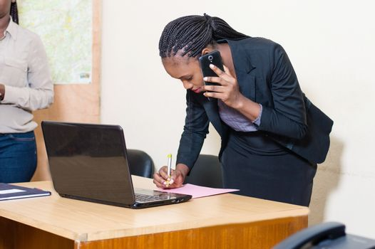 Young businesswoman on the phone taking notes with a cell phone in front of her on the table.