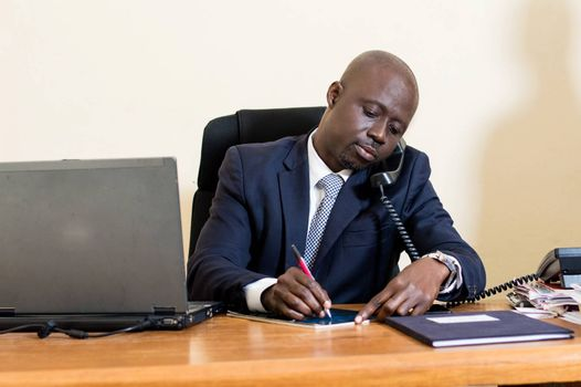 Young businessman sitting, takes notes on the phone.