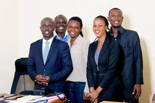 Group of happy business people posing together at the service watching the camera