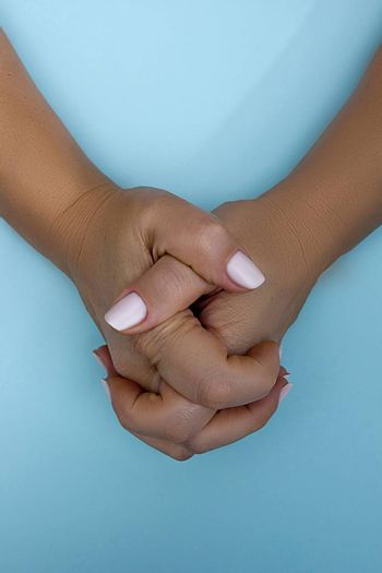 Female hands with intertwined fingers on a blue background