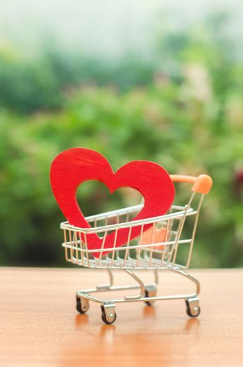 Red wooden heart in the trading cart. concept of buying love. nature background. Health care and purchase of medicines. Health care budget. Love for shopping. Favorite store. Buy love and happiness.