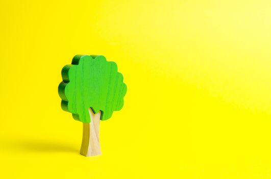 Toy wooden tree on an yellow background. Minimalism and the concept of environmental conservation. lungs of the planet. Family tree, a symbol of strength and wisdom. Illegal deforestation.