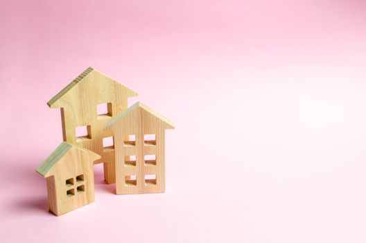 Wooden houses on a pink background. The concept of the city or town. Investing in real estate, buying a house. Management and business management, market coverage. Construction of buildings.