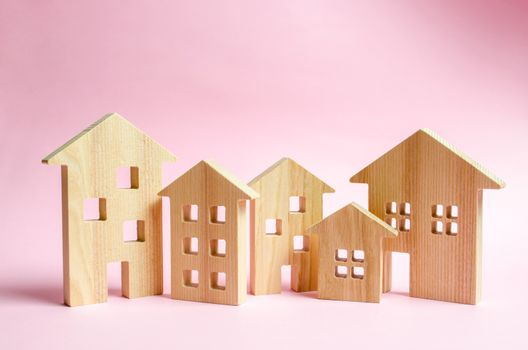 A lot of wooden houses on a pink background. The concept of the city or town. Investing in real estate, buying a house. Management and business management, market coverage. Construction of buildings.