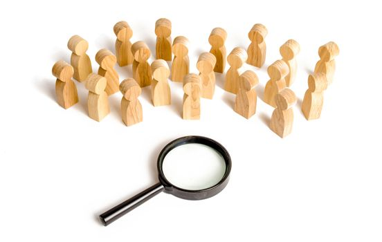 Huge crowd of people stand near a magnifying glass on a white background. Search for work. Human resources, management. concept of the search for people and workers. Sociology and psychology