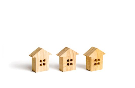 Three wooden figurines of houses on a white background. Minimalism and copy space. The concept of real estate, housing, buying or selling, renting. Settlement or community. Building construction.