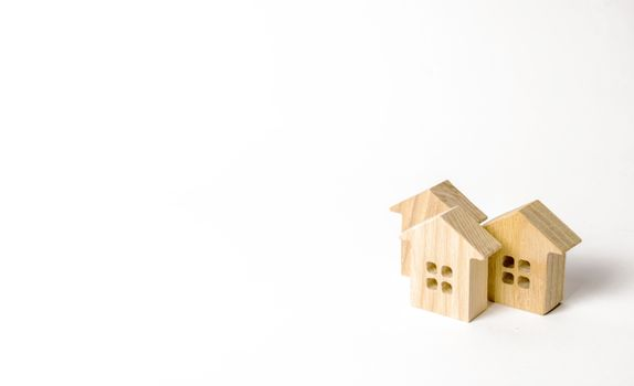 Wooden figurines of houses on a white background. Minimalism and copy space. The concept of real estate, housing, buying or selling, renting. Settlement or community. Building construction.