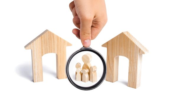 Magnifying glass is looking at the family with children stand between two houses and make a decision, they make a choice. the designation of the future family. The search for a new home.