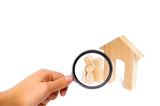 Magnifying glass is looking at the young family with children is standing near a wooden house. The concept of a strong family, the continuation of the family. A new house for the family.