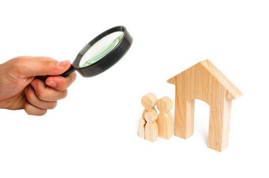 Magnifying glass is looking at the young family with children is standing near a wooden house. A new house for the family. The concept of a strong family, the continuation of the family.
