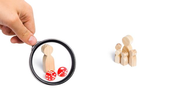 Magnifying glass is looking at the People are standing near dice. The family stands near the dice cubes. The concept of gambling, the dependence on gambling. Destruction of the family. Random