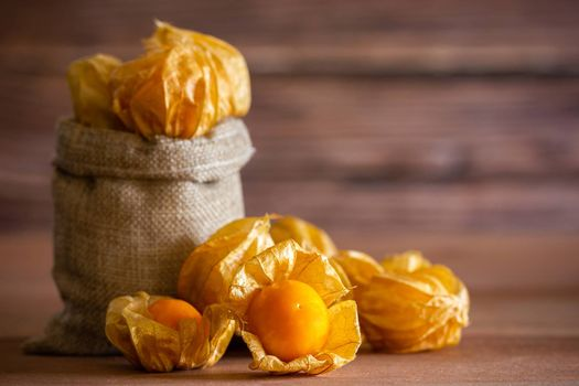Cape gooseberry in burlap bags. Concept of health care or herb. Closeup and copy space for text.