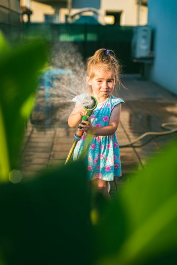 Happy 2-3 year old girl with garden hose water the plants plants. Activity for chirldren at summer concept.