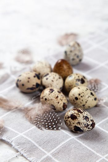 pile of Easter quail eggs on gray fabric rag on white concrete background. space for text