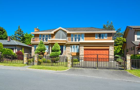 Residential house with wide garage, landscaped yard, and metal fence in front