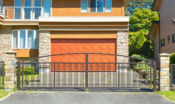 Wide garage door behind closed metal gates.