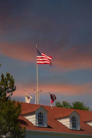 The American flag flying against a clear blue sky over a red roof with dormers