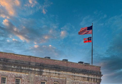 American and Georgia Flag flying over an old brick building