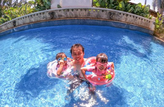 Asian sibling sisters playing in swimming pool with family in a hot summer day. Family lifestyle in vacation.