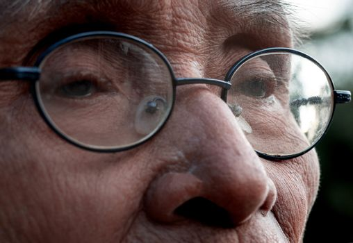 Close-up of the eyes of an elderly man wearing glasses sitting vacant in a sunny garden with a natural bokeh background. selective focus.