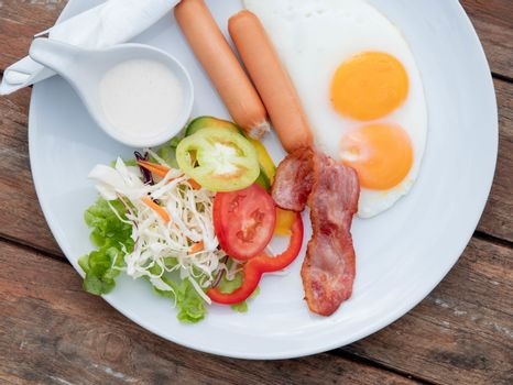 American breakfast with sunny side up fried eggs, bacon, sausage and vegetable salad on white dish on wooden table background.