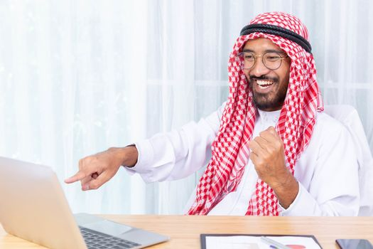 Arabian businessman smile and happy from message his computer notebook in his office