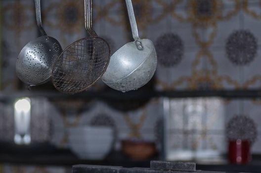hanging utensils in abandoned kitchen of a guest house