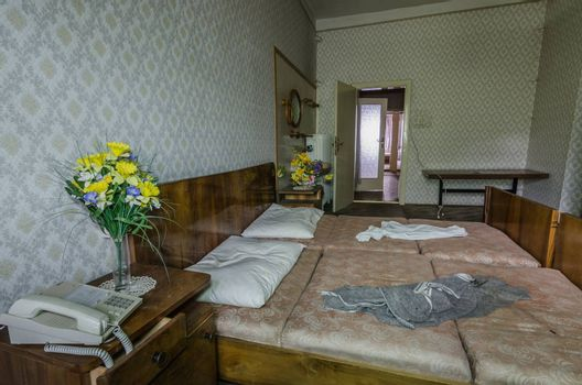 yellow flowers near a bed in abandoned hotel room