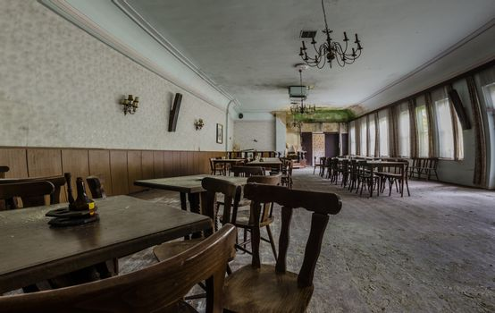 armchairs and tables in a ballroom in abandoned guesthouse