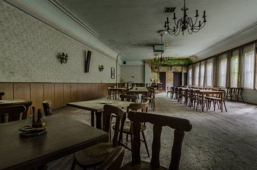 abandoned ballroom with tables and armchair